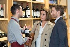 Πωλητής που προσφέρει το μπουκάλι κόκκινο κρασί στο νέο ζεύγος Στοκ Φωτογραφία