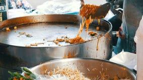 Πωλητής των παραδοσιακών ταϊλανδικών νουντλς ρυζιού τηγανητών τροφίμων οδών με τα αυγά, το κοτόπουλο και τους νεαρούς βλαστούς ασ φιλμ μικρού μήκους
