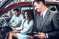 Πωλητής των προσδιδόντων γόητρο χαρακτηριστικών αφήγησης εμποριών αυτοκινήτων του οχήματος Νέα ερωτευμένη συνεδρίαση ζευγών στο σ στοκ εικόνες με δικαίωμα ελεύθερης χρήσης