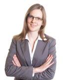 Πωλήτρια με eyeglasses σε ένα γκρίζο σακάκι που εξετάζει τη κάμερα Στοκ εικόνα με δικαίωμα ελεύθερης χρήσης