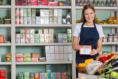 Πωλήτρια που επιδεικνύει Pricetag στο μανάβικο Στοκ εικόνες με δικαίωμα ελεύθερης χρήσης