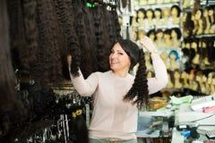 Πωλήτρια που προσφέρει τις περούκες Στοκ Εικόνα