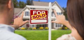Πωλημένος για το σημάδι πώλησης, το σπίτι και τα στρατιωτικά πλαισιώνοντας χέρια ζεύγους Στοκ φωτογραφία με δικαίωμα ελεύθερης χρήσης