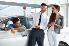 Πωλητής αυτοκινήτων που δίνει ένα κλειδί από το νέο αυτοκίνητο στους νέους ιδιοκτήτες Στοκ Φωτογραφία