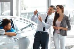 Πωλητής αυτοκινήτων που δίνει ένα κλειδί από το νέο αυτοκίνητο στους νέους ιδιοκτήτες Στοκ φωτογραφίες με δικαίωμα ελεύθερης χρήσης
