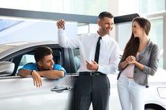 Πωλητής αυτοκινήτων που δίνει ένα κλειδί από το νέο αυτοκίνητο στους νέους ιδιοκτήτες Στοκ Εικόνες