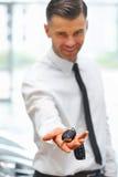 Πωλητής αυτοκινήτων που δίνει το κλειδί του νέου αυτοκινήτου στην αίθουσα εκθέσεως Στοκ Εικόνα