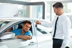 Πωλητής αυτοκινήτων που παραδίδει το νέο κλειδί αυτοκινήτων στον πελάτη στην αίθουσα εκθέσεως Στοκ Φωτογραφίες
