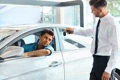 Πωλητής αυτοκινήτων που παραδίδει το νέο κλειδί αυτοκινήτων στον πελάτη στην αίθουσα εκθέσεως Στοκ εικόνα με δικαίωμα ελεύθερης χρήσης