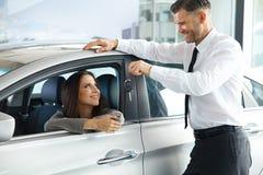 Πωλητής αυτοκινήτων που παραδίδει το νέο κλειδί αυτοκινήτων στον πελάτη στην αίθουσα εκθέσεως Στοκ Εικόνες
