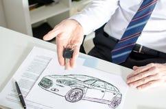 Πωλητής αυτοκινήτων που παρουσιάζει ένα κλειδί και σχέδιο αυτοκινήτων Στοκ Φωτογραφίες