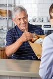 Πωλητής που δίνει την τσάντα παντοπωλείων συλλέγοντας τα μετρητά στοκ εικόνες