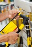 Πωλητής που εξετάζει Hacksaw στο κατάστημα Στοκ εικόνα με δικαίωμα ελεύθερης χρήσης