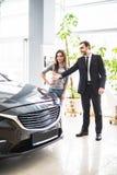 Πωλητής που παρουσιάζει όχημα στην πιθανή γυναίκα πελατών στον αντιπρόσωπο στοκ φωτογραφίες