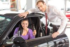 Πωλητής που πωλεί ένα αυτοκίνητο στον ευτυχή πελάτη Στοκ Εικόνες