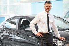 Πωλητής που στέκεται στο μαγαζί λιανικής πώλησης αυτοκινήτων Αίθουσα εκθέσεως αυτοκινήτων Στοκ Εικόνα