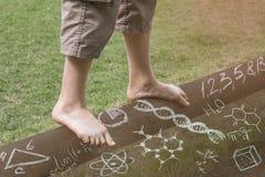 Πόδια αγοριών ` s σε μια ακτίνα ισορροπίας πριν από τους τύπους στοκ εικόνα