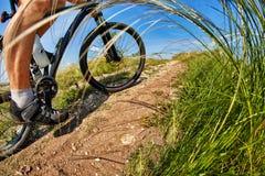 πόδια ατόμων ποδηλατών που οδηγούν το ποδήλατο βουνών στο υπαίθριο ίχνος στο ηλιόλουστο λιβάδι Στοκ Εικόνα