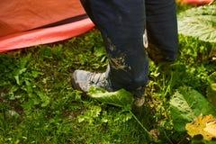 Πόδια ατόμων ` s στις βρώμικες μπότες τουριστών δίπλα στη σκηνή Στοκ φωτογραφία με δικαίωμα ελεύθερης χρήσης