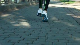 Πόδια γυναικών κινηματογραφήσεων σε πρώτο πλάνο που το τρέξιμο στο ηλιόλουστο πάρκο πόλεων σε σε αργή κίνηση απόθεμα βίντεο