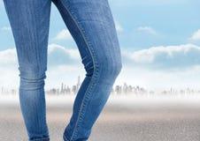 Πόδια γυναικών ` s μπροστά από το τοπίο πόλεων στα τζιν Στοκ Εικόνες