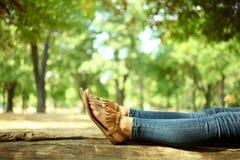 Πόδια γυναικών ` s σε έναν ξύλινο πάγκο Στοκ Εικόνες