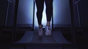 Πόδια γυναικών s στα άσπρα πάνινα παπούτσια και περικνημίδες που treadmill στο αργό MO απόθεμα βίντεο