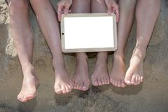 Πόδια διάφορων κοριτσιών στην παραλία άμμου με την άσπρη κενή κενή διαφήμιση μηνυμάτων πινάκων διαφημίσεων foir στοκ φωτογραφία με δικαίωμα ελεύθερης χρήσης