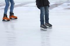 Πόδια δύο ανθρώπων που κάνουν πατινάζ στην αίθουσα παγοδρομίας πάγου Στοκ Εικόνα