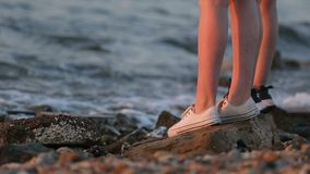 Πόδια δύο θηλυκών τουριστών που στέκονται στην παραλία το βράδυ φιλμ μικρού μήκους