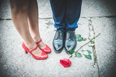 Πόδια ενός άνδρα στα μαύρα παπούτσια και των γυναικών στα κόκκινα παπούτσια Ρομαντικός ομο Στοκ Εικόνες