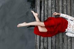 Πόδια ενός κοριτσιού σε μια κόκκινη φούστα σε μια γέφυρα στοκ φωτογραφία με δικαίωμα ελεύθερης χρήσης