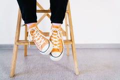 Πόδια ενός κοριτσιού στα πορτοκαλιά πάνινα παπούτσια και τις ρόδινες κάλτσες Ο έφηβος στα πάνινα παπούτσια και τα σκοτεινά τζιν κ Στοκ εικόνες με δικαίωμα ελεύθερης χρήσης