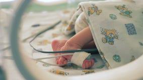 Πόδια ενός μικρού παιδιού που βρίσκεται σε μια μονάδα νοσοκομείων στενό σε έναν επάνω φιλμ μικρού μήκους