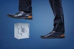 Πόδια επιχειρηματία στα παπούτσια δέρματος έτοιμα να συνθλίψουν ένα ανοικτό γκρι χρηματοκιβώτιο μετάλλων στοκ εικόνες