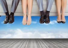 Πόδια και πόδια λαών που κρεμούν από τον επιπλέοντα καναπέ πέρα από τον ουρανό Στοκ Εικόνα
