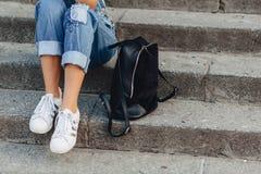 Πόδια και νέο όμορφο κορίτσι τσαντών με τη συνεδρίαση χαρτοφυλάκων στα σκαλοπάτια στοκ φωτογραφία με δικαίωμα ελεύθερης χρήσης