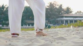 Πόδια κινηματογραφήσεων σε πρώτο πλάνο της ανώτερης γυναίκας που ασκεί tai chi στην άμμο απόθεμα βίντεο