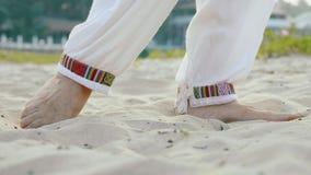 Πόδια κινηματογραφήσεων σε πρώτο πλάνο της ανώτερης γυναίκας που ασκεί tai chi στην άμμο φιλμ μικρού μήκους