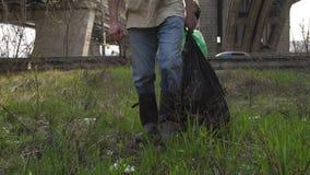 Πόδια κινηματογραφήσεων σε πρώτο πλάνο του ατόμου που περπατά με τις τσάντες απορριμμάτων απόθεμα βίντεο
