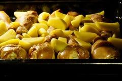 Πόδια κοτόπουλου με τις πατάτες που ψήνονται στοκ εικόνα με δικαίωμα ελεύθερης χρήσης