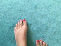 Πόδια με την κόκκινη στιλβωτική ουσία καρφιών στον κυανό τάπητα Στοκ φωτογραφία με δικαίωμα ελεύθερης χρήσης