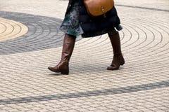 Πόδια μιας γυναίκας που περπατά στο ομόκεντρο πεζοδρόμιο κύκλων Στοκ Φωτογραφίες