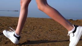 Πόδια μιας γυναίκας στα πάνινα παπούτσια που τρέχουν σε μια παραλία φιλμ μικρού μήκους