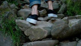 Πόδια μιας γυναίκας στα τζιν και τη διασταύρωση, που περπατούν μόνο σε μια πορεία βουνών με πολλές πέτρες απόθεμα βίντεο