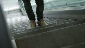 Πόδια νεαρών άνδρων κινηματογραφήσεων σε πρώτο πλάνο άσπρα snickers στην κυλιόμενη σκάλα φιλμ μικρού μήκους