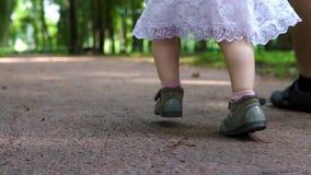 Πόδια παιδιών ` s στα σανδάλια που τρέχουν μέσω του πάρκου κλείστε επάνω απόθεμα βίντεο
