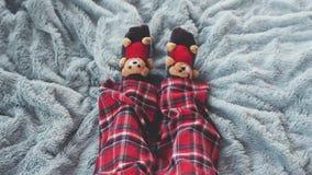 Πόδια παιχνιδιού στο σπίτι ντυμένες στις κρεβάτι κάλτσες με τις χαριτωμένες teddy αρκούδες στις πυτζάμες σε ένα μπλε κάλυμμα σε σ απόθεμα βίντεο