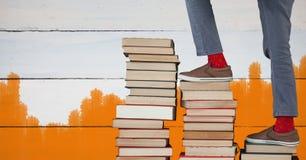 Πόδια που περπατούν επάνω τα βήματα βιβλίων και χρωματισμένο το πορτοκάλι υπόβαθρο Στοκ Φωτογραφία