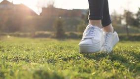 Πόδια που τρέχουν την υπαίθρια ενεργό φύση πάνινων παπουτσιών πάρκων ηλιοβασιλέματος χλόης απόθεμα βίντεο